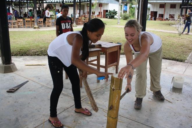 Savannah splitting bamboo with a local girl